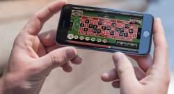 Händer som håller mobil med roulette